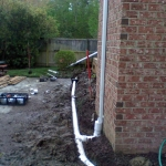 Drains being installed with 4'' PVC pipe. This allows for great drainage, that should never clog. Notice how the downspout is relatively sealed where it is connected to the pipe.